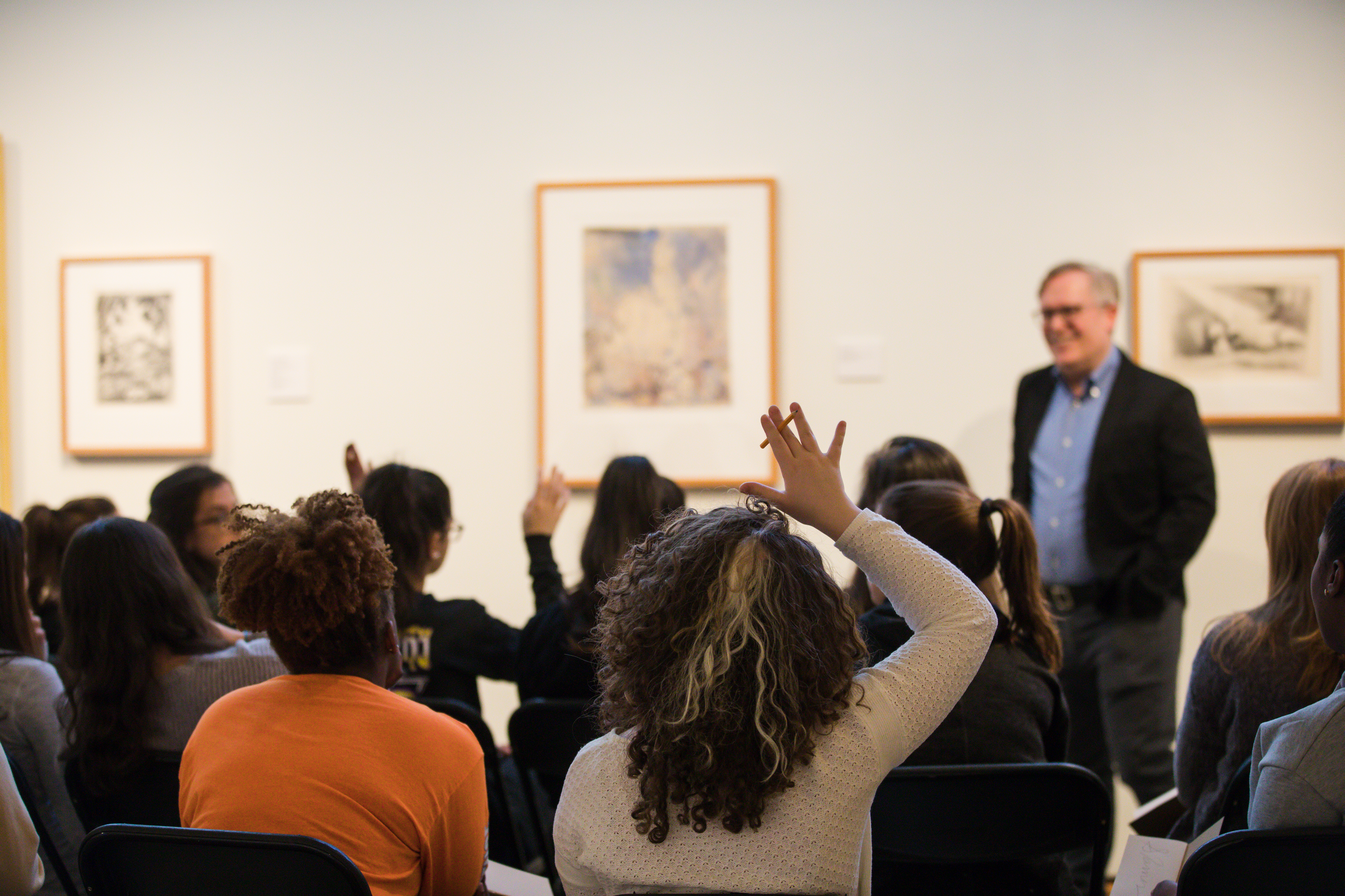 group of college students sitting on chairs in front of three works of art and a professor. One student has her hair raised.