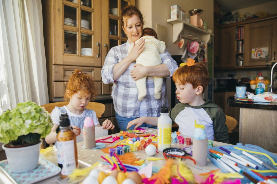 woman holding baby while two young children create art
